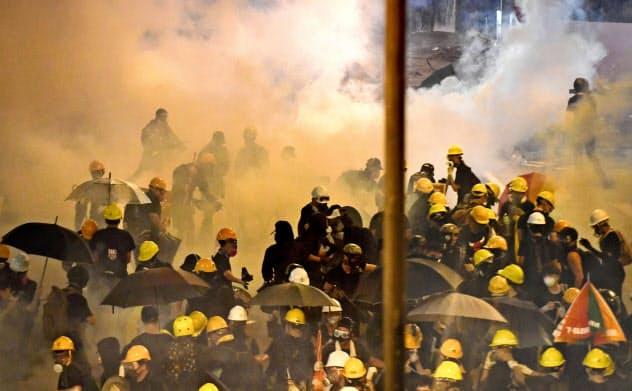 催涙弾の白煙が立ちこめる中、逃げ惑う若者ら(21日、香港)=共同