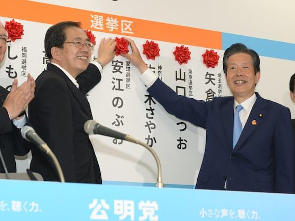当選を確実にした候補者名にバラをつける山口代表(右から2人目)ら=21日、公明党本部
