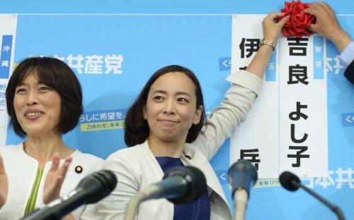 当選を確実にし、自身の名前に花をつける吉良佳子氏(右)(21日、共産党本部)