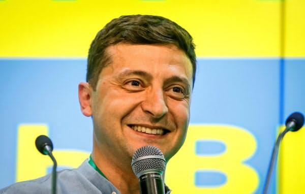 議会選の出口調査で与党「国民の奉仕者」が第1党と伝えられて喜ぶゼレンスキー大統領(21日、キエフ)=ロイター