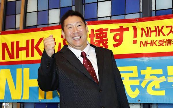 比例代表で当選が決まり、笑顔でポーズをとる政治団体「NHKから国民を守る党」の立花孝志代表(22日午前、東京・赤坂)=共同