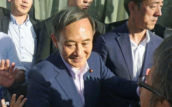 参院選立候補者の応援に駆け付け、聴衆とタッチする菅官房長官(新潟市)=共同