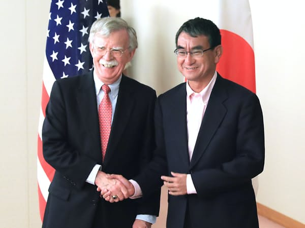会談前にボルトン米大統領補佐官(左)と握手する河野外相(22日、外務省)