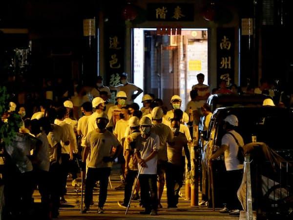 22日未明、白いTシャツ姿の集団が香港のデモ参加者らに暴行した=ロイター