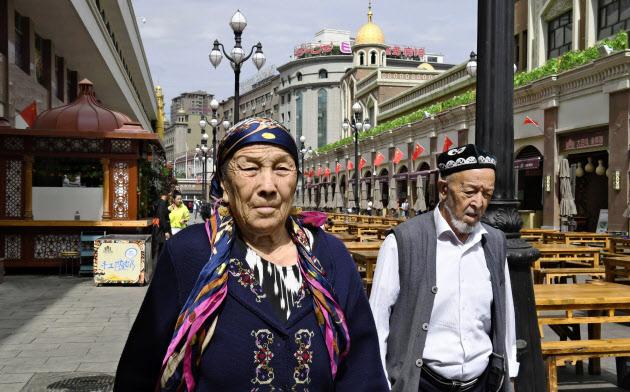 ウイグル文化の行方は…(中国新疆ウイグル自治区ウルムチを歩くウイグル族の男女、5日)=共同