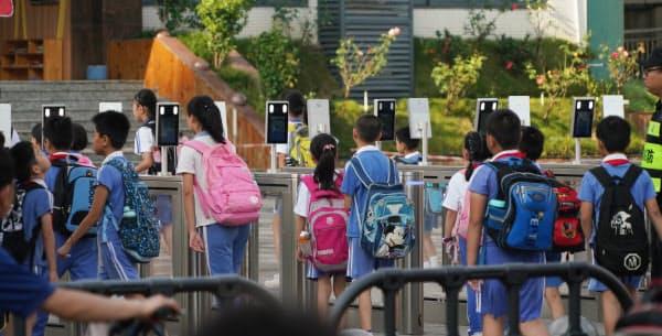 小学校の校門に設置された顔認証ゲートを通って登校する児童(中国・深圳)