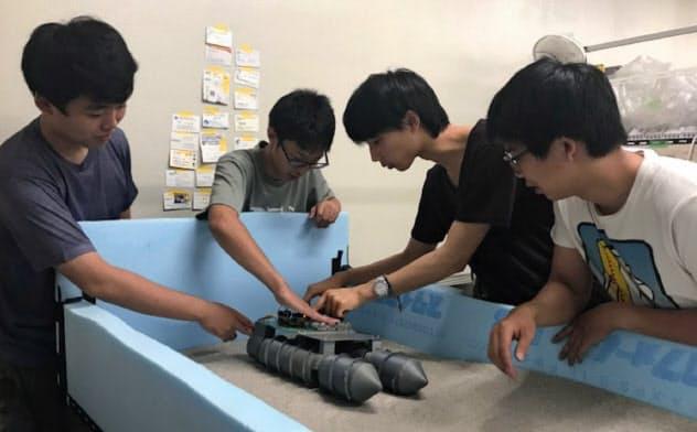 月面を模して砂を敷き、探査機の走行実験を行う都立産技高専の学生たち
