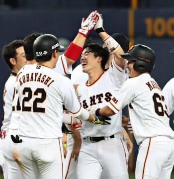 9回、代打でサヨナラ二塁打を放ち、ナインに祝福される巨人・重信=中央(23日、京セラドーム)=共同