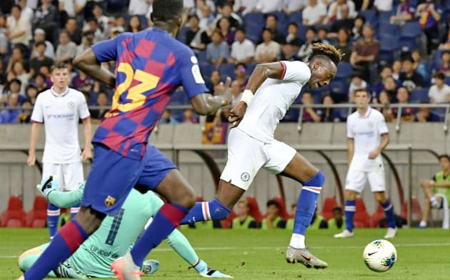 バルセロナ―チェルシーの前半、先制ゴールを決めるチェルシーのエーブラハム=右(23日、埼玉スタジアム)=共同
