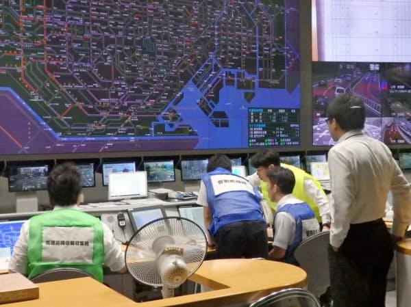 警視庁交通管制センターでは職員らがモニターを見ながら、頻繁に相談(24日午前7時すぎ、東京都港区)