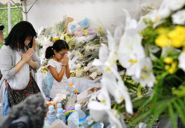 京都アニメーションのスタジオ近くの献花台を訪れ手を合わせる人たち(25日、京都市伏見区)