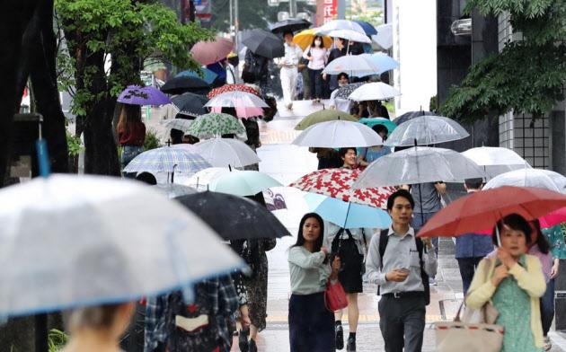 梅雨空の下、傘を差して歩く人たち(7月7日、名古屋市中区)