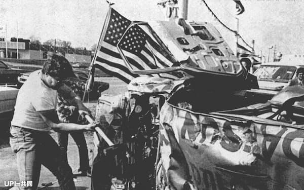 デトロイトの自動車工場を解雇され、日本車にハンマーを振るう元従業員(1980年5月、米ミシガン州)=共同