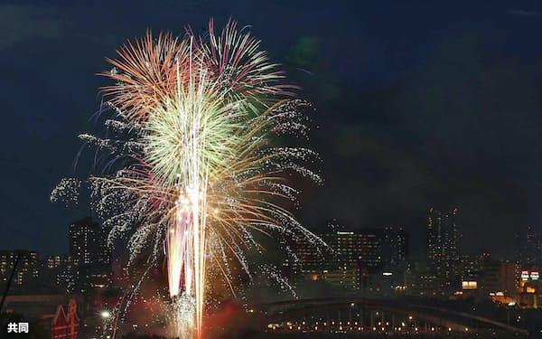 奉納花火が夜空を彩り、大川を船が行き交う天神祭の「船渡御」(25日、大阪市、多重露光)=共同