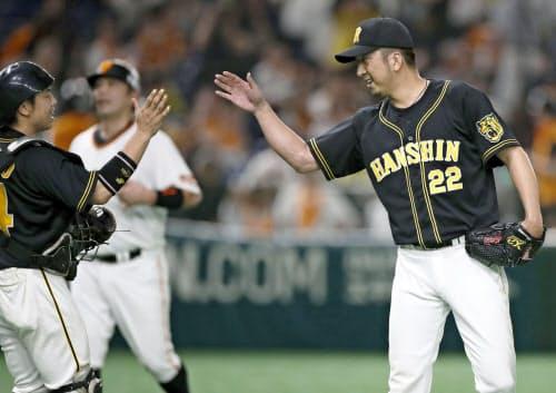 巨人に連勝、捕手梅野とタッチを交わす阪神・藤川=右(27日、東京ドーム)=共同