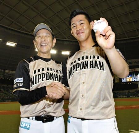 プロ初勝利を挙げ、ウイニングボールを手に栗山監督(左)と握手を交わす日本ハム・北浦(27日、メットライフドーム)=共同