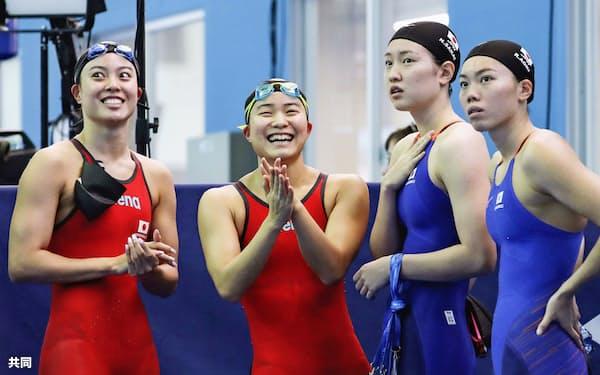 女子400メートルメドレーリレー予選の順位を確認する(左から)大本、牧野、酒井、青木玲。東京五輪出場枠を獲得した(28日、光州)=共同