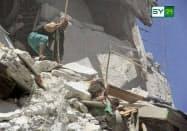 空爆で倒壊した建物の下敷きになったまま妹のトゥカちゃん(右)を助けようとする姉リハムちゃん(中央)。父親(左上)は姉妹に向かって何かを叫んでいる=24日、シリア・イドリブ県(シリア反体制派メディア「SY24」提供・共同)