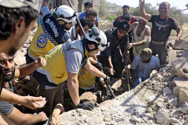 シリア北西部イドリブ県で空爆された建物のがれきから犠牲者を捜索する市民組織、シリア民間防衛隊(ホワイトヘルメッツ、25日)=ホワイトヘルメッツ提供・AP