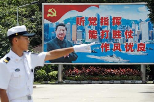 習国家主席の看板の前に立つ中国人民解放軍の兵士(2019年6月30日、香港)=ロイター