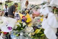 事件現場近くの献花台で手を合わせる男性(30日午後、京都市伏見区)=共同