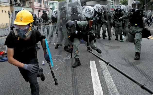 7月27日、新界地区・元朗でデモ参加者が襲撃された事件に抗議するデモの最中に、参加者の一人を追いかける警察隊=ロイター