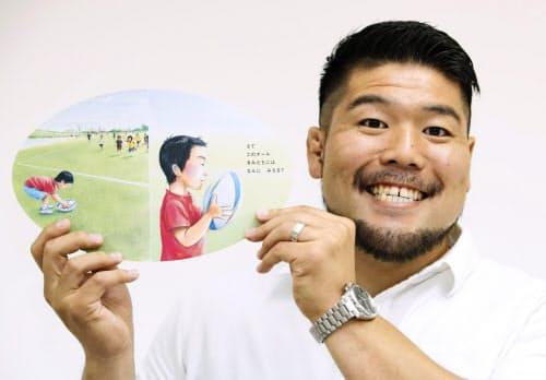 自身が発案した絵本「らくがきボール」を手に、笑顔を見せる畠山健介選手=共同