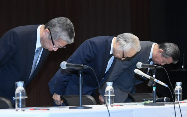 記者会見で頭を下げる日本郵政の長門正貢社長(中)ら(31日、東京・大手町)