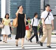 強い日差しの中を歩く人たち(31日、東京都千代田区)