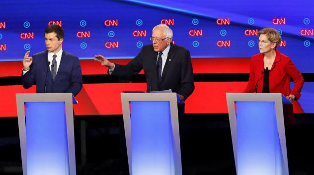 30日の米民主党討論会に出席するサンダース上院議員(中)ら大統領選候補(中西部ミシガン州デトロイト)=AP