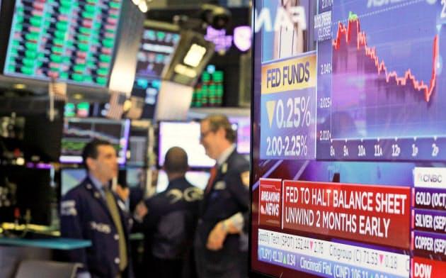 ニューヨーク証券取引所で利下げを伝えるニュース画面(31日)=ロイター