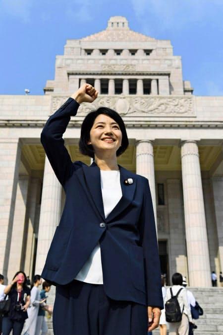 初登院し、国会議事堂を背にポーズをとる立憲民主党の石垣のり子氏(1日)=共同