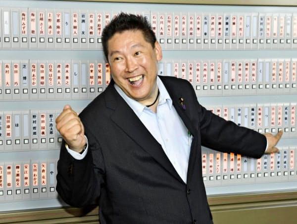 国会に初登院し、登院板のボタンを押すNHKから国民を守る党の立花孝志氏(1日)=共同