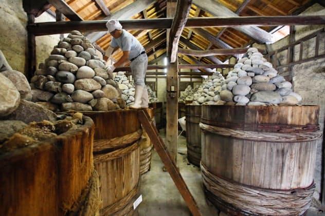 味噌を入れた木桶に重しの石を積み上げて熟成させる(愛知県岡崎市のまるや八丁味噌)