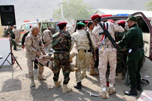 攻撃されたイエメン軍基地で負傷者を救助する兵士(1日、アデン)=ロイター