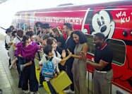 ミッキーマウスとミニーマウスを装飾した九州新幹線の列車に乗り込む招待客ら(1日、JR博多駅)=共同