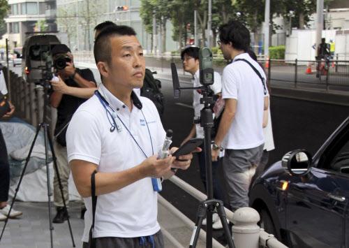 東京五輪のマラソンコースで、気温などを測定するウェザーニューズの職員(2日午前、東京都内)=共同