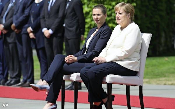 椅子に座って外国首脳を歓迎するメルケル独首相(右)=AP