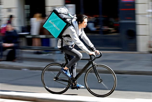 料理宅配サービス「デリバルー?#24037;?#39135;事を運ぶ青年(パリ)=ロイター