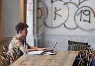 人材流出の防止策だが、効果は疑問視されている(1日、ポーランド・ワルシャワのカフェでノートパソコンに向かう男性)=AP・共同