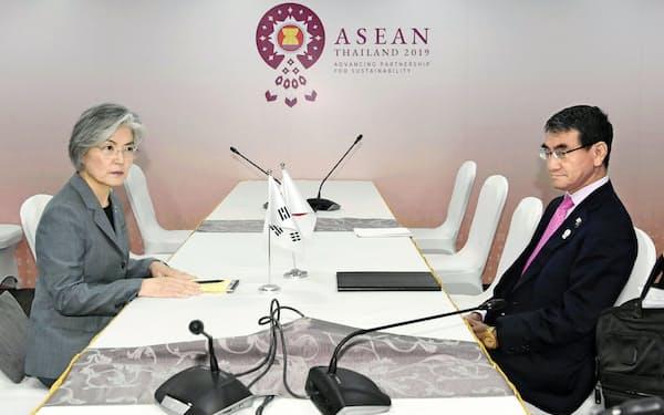 日韓両政府の対立は激化の一途をたどっている。(康京和外相(左)との会談に臨む河野外相、1日、バンコク)=共同