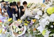 事件現場近くに設置された献花台で手を合わせる人たち(3日、京都市伏見区)=共同