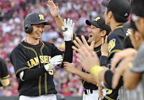 3回、本塁打を放ちナインに迎えられる阪神・近本(3日、マツダ)=共同