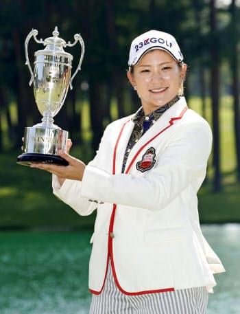 通算13勝目を挙げ、優勝トロフィーを手に笑顔の成田美寿々(4日、鳴沢GC)=共同