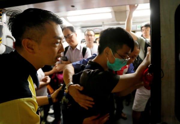 5日朝、香港で、地下鉄運行の妨害を試みる若者ら=ロイター