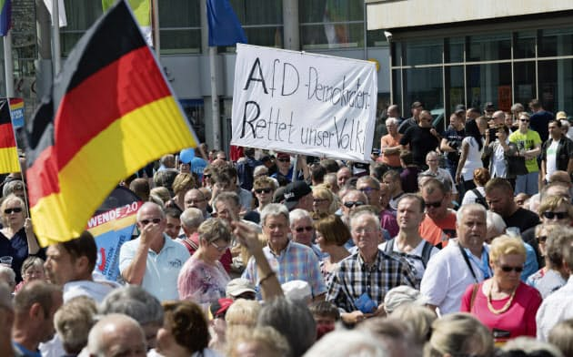 極右政党「ドイツのための選択肢(AfD)の名が入った幕を掲げる人々=AP