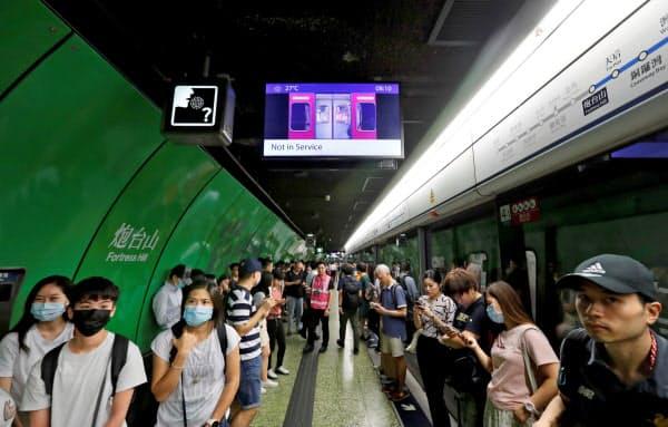 地下鉄の運行再開を待つ乗客ら(5日、香港)=ロイター