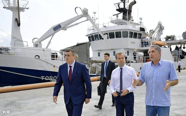 8月2日に択捉島を訪れたロシアのメドベージェフ首相(右から2人目)=タス共同