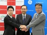 記者発表で握手するGEヘルスケア・ジャパンの多田社長(右)ら(5日、東京都内)