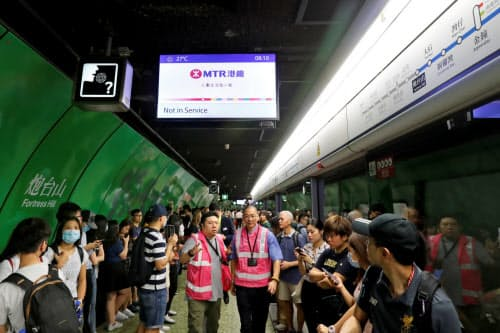 デモによる混乱でまひした地下鉄の運行再開を待つ乗客ら(5日、香港=ロイター)